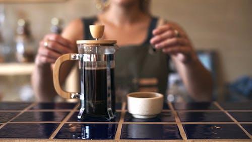 A Barista Serving a Brewed Coffee