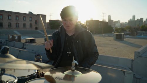 A Man Playing the Drums at a Rooftop