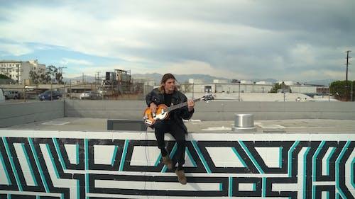 A Man Playing a Bass Guitar
