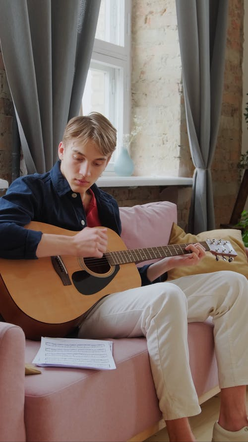 A Young Man Playing an Acoustic Guitar