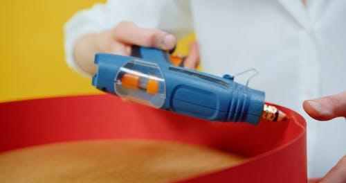 A Woman Using A Glue Gun