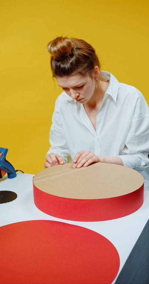 A Woman Gluing The Edges Of A Paper Craft