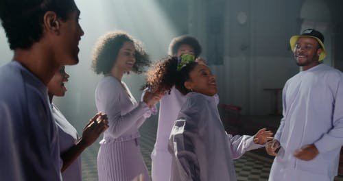 A Group Of Young People Singing And Dancing