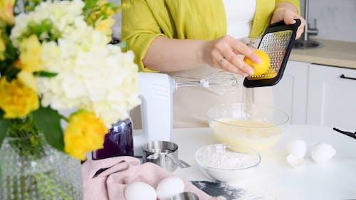A Woman Grating Lemon into the Batter