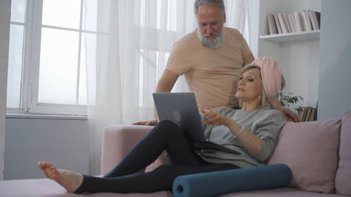 Elderly Couple Having a Conversation while Looking at a Laptop