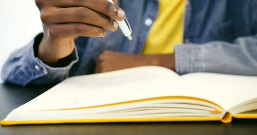 A Person Writing on a Notebook