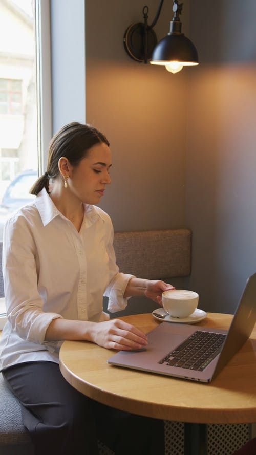 A Woman Drinking Coffee while Facing Her Laptop