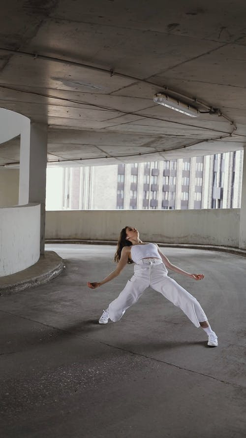 A Woman Dancing in a Parking Lot