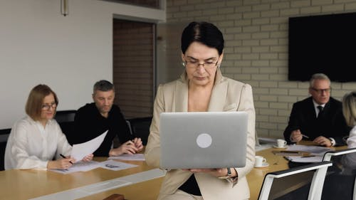Woman Using a Laptop While In a Meeting