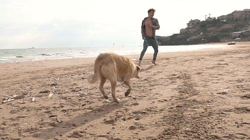 Man and Dog Running at the Beach