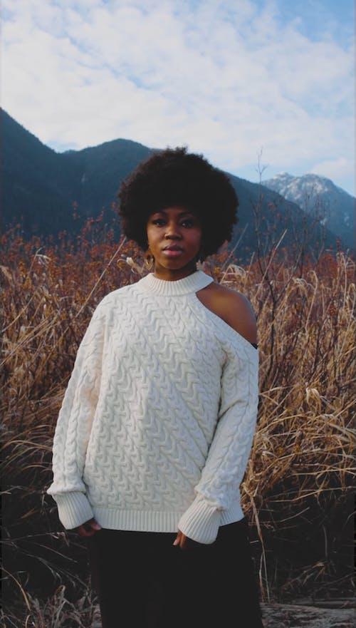 An Afro Woman on Grass Field