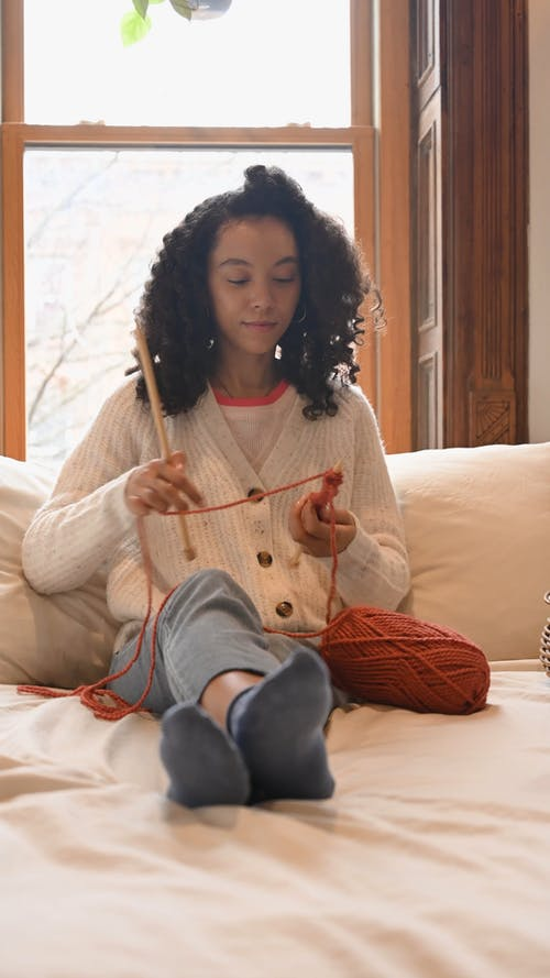 Woman Knitting while Sitting on Bed