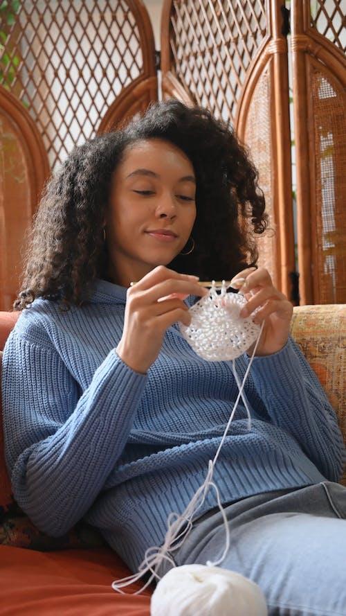 Woman Wearing Blue Sweater Crocheting a Yarn