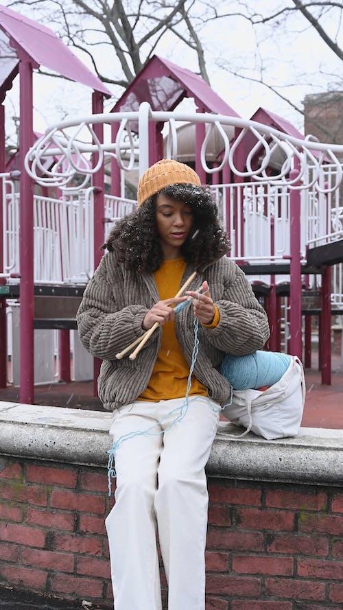 Woman Knitting at a Playground