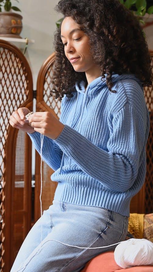 Woman Wearing Knitted Sweater Crocheting a Yarn