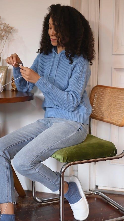 Woman Sitting on Chair Crocheting a Yarn
