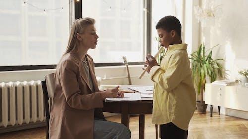 A Teacher Teaching a Boy How to Play the Flute