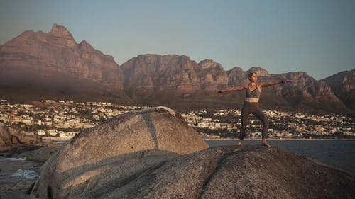 Woman Doing Yoga Over A Rock