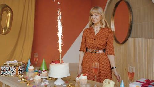 Woman Blowing Birthday Cake