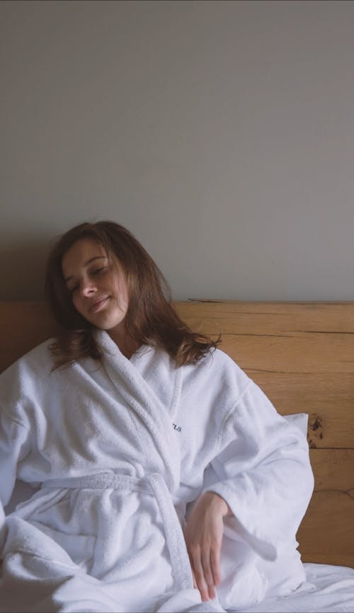 A Woman Stretching Her Arms while Sitting on Bed