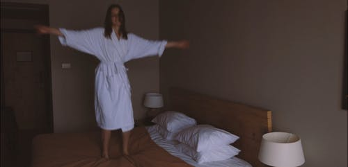 A Woman Jumping on the Bed and Having Fun