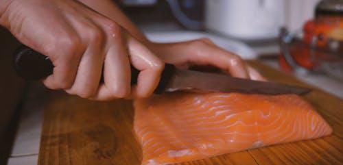 Person Slicing the Salmon
