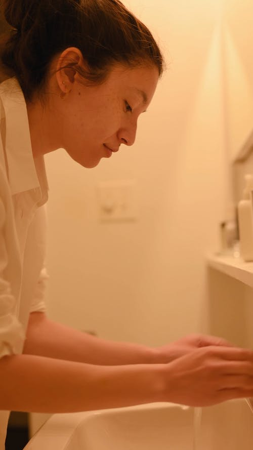 Side View of a Woman Washing her Face in a Bathroom