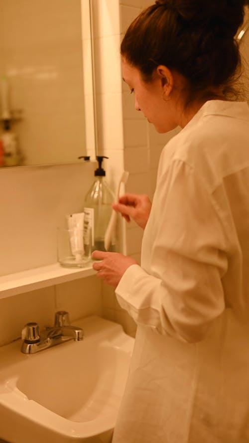 Woman Washing Her Toothbrush