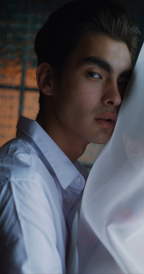 Man Hugging Woman Behind Sheer Curtain