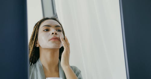 Woman Putting On Facial Care