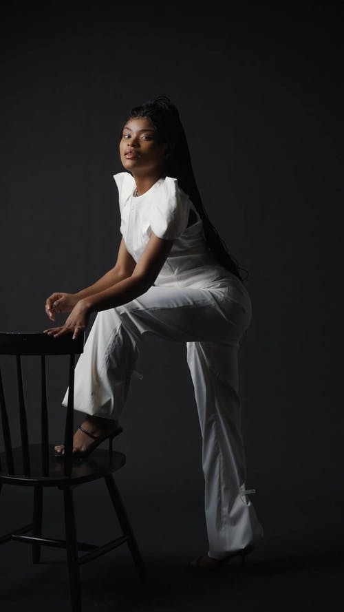 Woman in White Clothing Standing Near a Chair