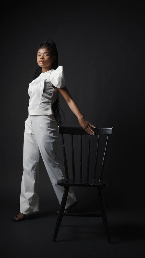 A Woman Posing while Sitting on a Chair