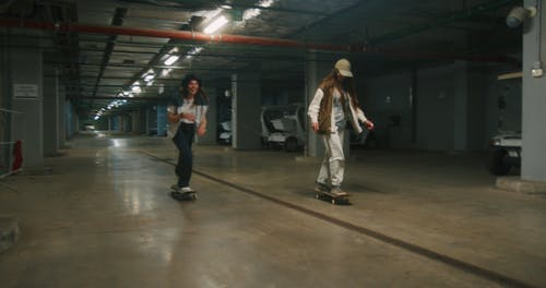 Two Females Skating in a Parking Area