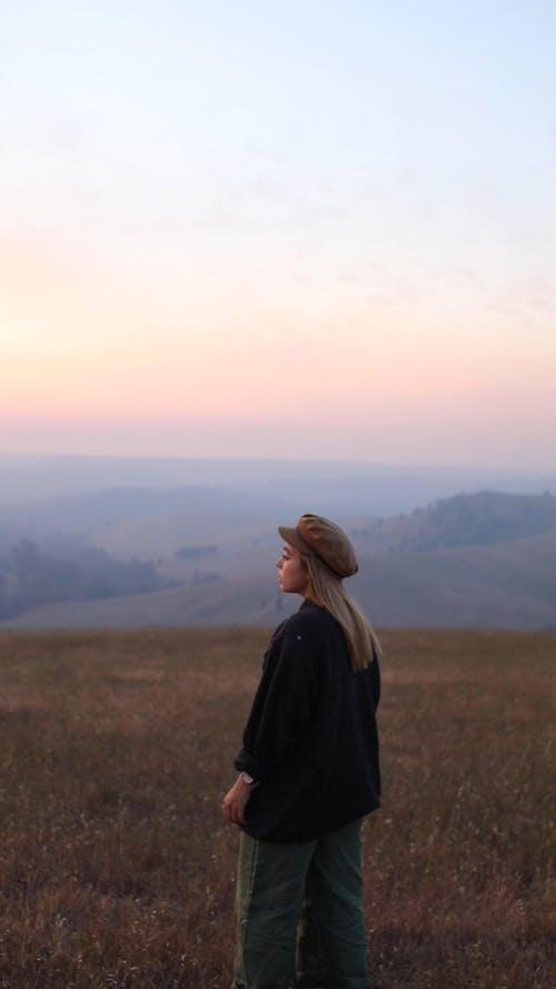 Woman Standing on a Grass Field