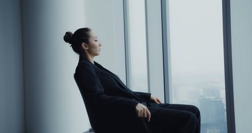 A Businesswoman Looking into a Glass Window while Sitting in a Chair