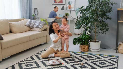 Woman using Smartphone While Holding Baby Girl