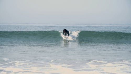 A Man Surfing at the Beach