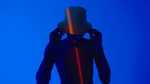 Shirtless Man With Hat Under Blue Light