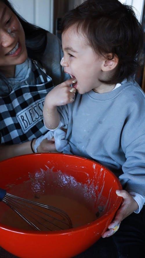 A Child Tasting a Batter