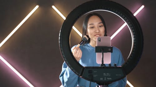 Woman Video Recording using Smartphone while Applying Makeup