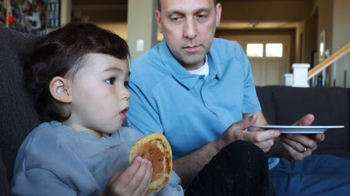 A Child Eating  Pancake with Her Father