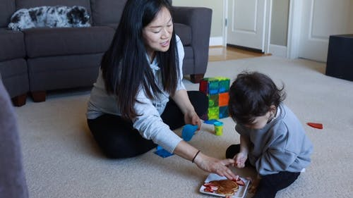 A Child Playing While Eating With Her Mom