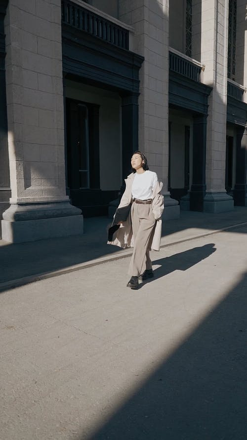 Woman Walking Outside the Architectural Building