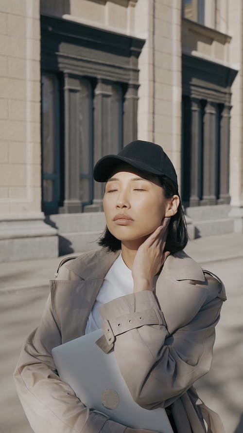 Woman with a Black Cap Posing with an Architectural Background