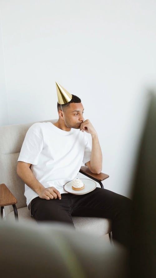 Man Wearing Party Hat Sitting on a Chair