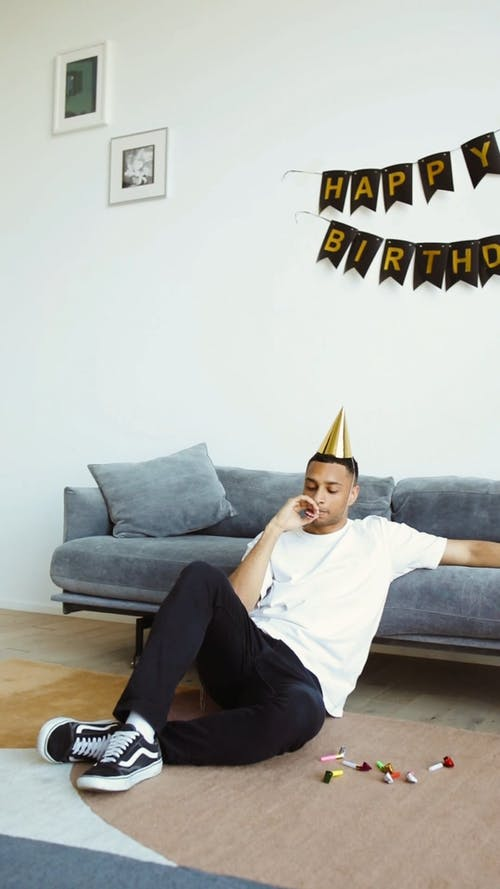 Man Wearing a Party Hat and Blowing a Party Horn