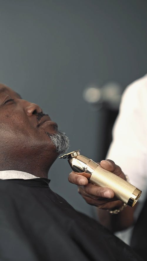 A Barber Trimming the Beard of a Client