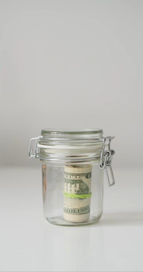 A Person Getting Money in a Jar