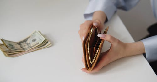 A Person Putting Money Inside a Wallet