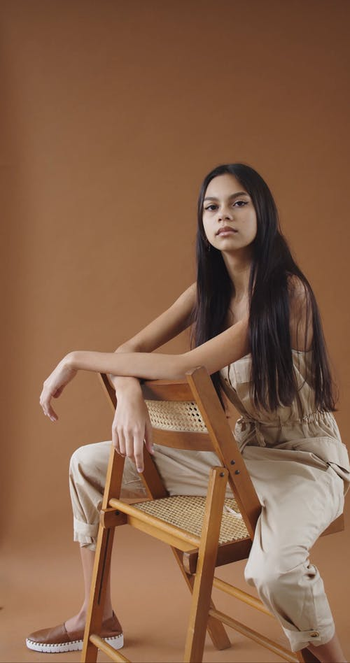 A Teen Woman Sitting on a Chair while Posing